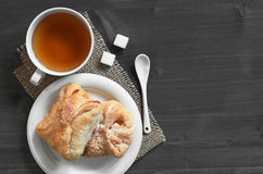 Tea and puff pastry. Cup of tea and sweet puff pastry with jam on a dark wooden table, top view with copy space Royalty Free Stock Photo
