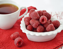 Tea and raspberries on a napkin Stock Photography