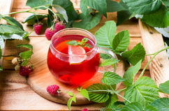 Tea with raspberries on a wooden table Stock Photos