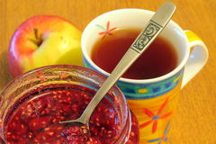 Tea with raspberry jam in jar and apple Royalty Free Stock Images