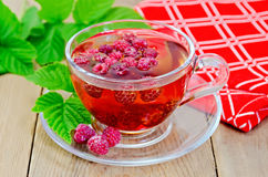Tea with raspberry and a napkin on board Stock Images