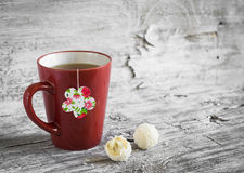 Tea in a red cup and a homemade tea bag on a light wooden background Stock Image