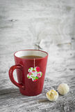 Tea in a red cup and a homemade tea bag on a light wooden background Royalty Free Stock Photo