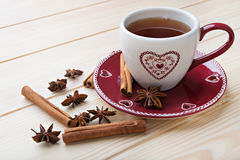 Tea in a red cup. Warm tea in the red cup on the wooden table Royalty Free Stock Image