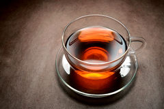 Tea. Red tea in glass cup steaming on brown Royalty Free Stock Image