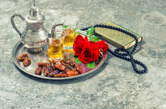 Tea, red rose flower, dates, holy book quran and rosary. Islamic. Holidays decoration. Ramadan kareem. Eid mubarak. Oriental hospitality concept. Retro style Stock Image