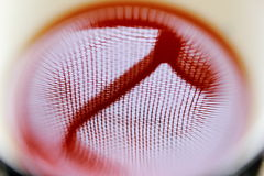 Tea reflects sunlight from a window. A macro of an eye ball like shaped abstract view of morning light from a window, having a netted mesh with grills, through a Stock Image