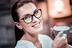 Cute bespectacled woman smiling and drinking tea. Tea and rest. Cute bespectacled satisfied woman having rest smiling and drinking tea Royalty Free Stock Photo