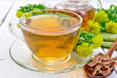 Tea of Rhodiola rosea in cup with spoon on board Royalty Free Stock Photo
