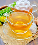 Tea of Rhodiola rosea in glass cup and teapot on sacking Royalty Free Stock Photo