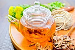 Tea of Rhodiola rosea in glass teapot on tray with spoon Stock Image
