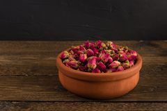 Tea rose buds in a clay pot isolated on wooden table on black. Background stock image
