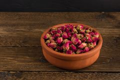 Tea rose buds in a clay pot isolated on wooden table on black. Background stock photos