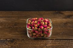 Tea rose buds in a clay pot isolated on wooden table on black. Tea rose buds in a glass drinking bowl isolated on wooden table on black background stock photos