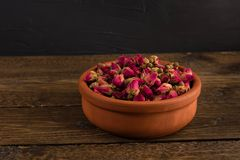 Tea rose buds in a clay pot on the wooden table isolated on black. Background stock photography
