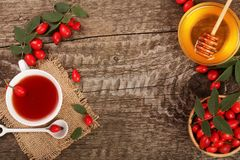 Tea with rose hips and honey on old wooden background with copy space for your text. Top view Stock Photos