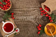 Tea with rose hips and honey on old wooden background with copy space for your text. Top view Stock Images