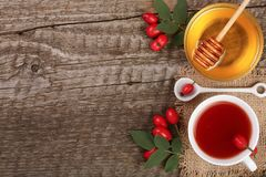 Tea with rose hips and honey on old wooden background with copy space for your text. Top view Stock Photography