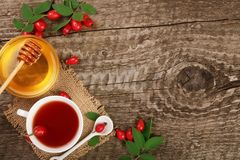 Tea with rose hips and honey on old wooden background with copy space for your text. Top view Royalty Free Stock Photos