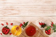 Tea with rose hips and honey on white wooden background with copy space for your text. Top view stock images