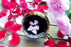 Tea with rose petals. Tea made from tea rose petals in a glass bowl on wooden rustic background Stock Photo