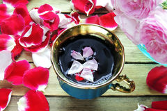 Tea with rose petals. Tea made from tea rose petals in a glass bowl on wooden rustic background Stock Photos