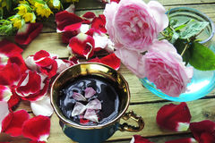 Tea with rose petals. Tea made from tea rose petals in a glass bowl on wooden rustic background Royalty Free Stock Photos