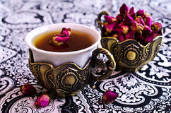 Tea roses in a beautiful Cup with Oriental motifs Stock Photo