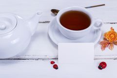 Tea in a round white cup with a saucer. On a white wooden background and an empty paper tag Royalty Free Stock Images