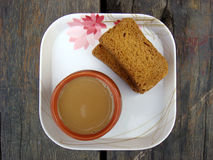 Tea and rusk in white plate. On wooden Stock Image
