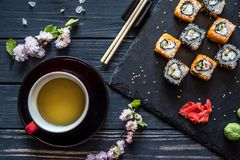 Tea, sakura and sushi. Tea in a cup, sakura branch, sushi, wasabi, marinated ginger on a black wooden background stock image