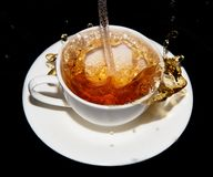 Tea saucer with splashes on a black background Stock Image
