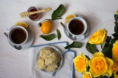 Tea and Scones with Yellow Roses on White Background Royalty Free Stock Images