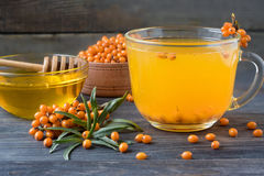 Tea of sea-buckthorn berries with honey and a branch on wooden background Stock Images