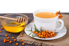 Tea of sea-buckthorn berries with honey on wooden table isolated  white background Royalty Free Stock Image
