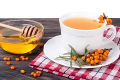 Tea of sea-buckthorn berries with honey on wooden table  white background. Tea of sea-buckthorn berries with honey on wooden table  on white background Stock Images