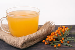 Tea of sea-buckthorn berries on wooden table  white background.  Stock Images