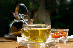 Tea is sent!. Cup of tea, jam and teapot on a table on open air Royalty Free Stock Photography