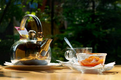 Tea is sent!. Cup of tea, jam and teapot on a table on open air Stock Image
