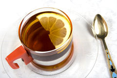 Tea series 2. A glass cup of tea with lemon and a teaspoon Royalty Free Stock Photography