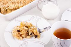 Tea served with traditional British apple or rhubarb crumble. A portion on a plate and crumble in a baking dish Stock Images