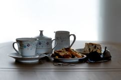 Tea Service & Fruit cake on a wooden table with the scene being backlit with natural light . The images a casual look with coins b royalty free stock images