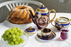 Tea service with marble cake and grapes Royalty Free Stock Photography