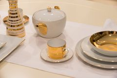 Tea service or set with pot, cup, saucer, plates. And vase with golden gilt served on white table cloth background. Tea party or ceremony concept stock photo