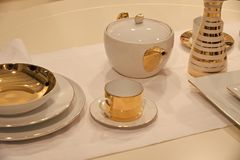 Tea service or set with pot, cup, saucer, plates. And vase with golden gilt served on white table cloth background. Tea party or ceremony concept royalty free stock photo