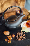 Tea serving. Black tea kettle with walnuts and star anise on black tabletop with glass of tea and fruit slices Royalty Free Stock Images