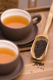 Tea serving in brown cups. With teapot and wooden cutlery Stock Photography