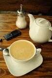 Tea set. Break for tea in cafe. A cup of tea, sugar bowl, spoon, teapot and cellphone on the table Stock Photography