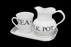 Tea set. Nice white dish set: tea cup, milk pot and bread plate with big black words as decoration, isolated on black background royalty free stock photo