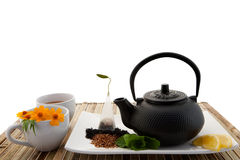 Tea Set. A view of a black tea pot and in a tray with herbs, and a white cup with flowers Stock Photos